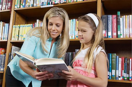 School girl reading book with teacher in library Stock Photo - Premium Royalty-Free, Code: 693-06020473