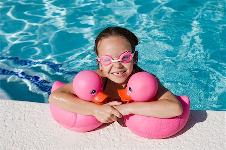 preteen girl wet clothes - Girl at Pool Side Holding Pink Rubber Ducks Stock Photo - Premium Royalty-Free, Code: 693-06020764