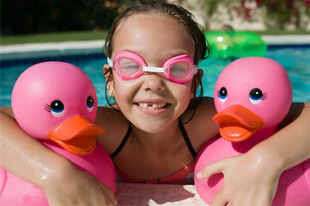 preteen girl wet clothes - Girl at Pool Side Holding Pink Rubber Ducks Stock Photo - Premium Royalty-Free, Code: 693-06020765