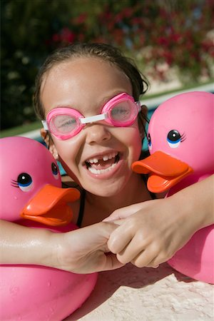 preteen girl wet clothes - Girl at Pool Side Holding Pink Rubber Ducks Stock Photo - Premium Royalty-Free, Code: 693-06020766