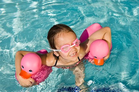 preteen girl wet clothes - Girl Floating Using Two Pink Rubber Ducks Stock Photo - Premium Royalty-Free, Code: 693-06020763