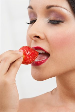 Woman eating strawberry Stock Photo - Premium Royalty-Free, Code: 693-06021794