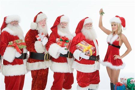Group of men dressed as Santa Claus, Mrs Claus holding mistletoe Stock Photo - Premium Royalty-Free, Code: 693-06021810