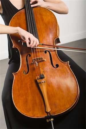 string - Mid section of woman bowing a cello Stock Photo - Premium Royalty-Free, Code: 693-06021837