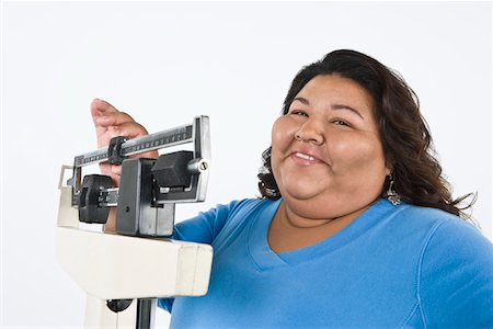 fat black woman - Woman using weight scales Stock Photo - Premium Royalty-Free, Code: 693-06021867