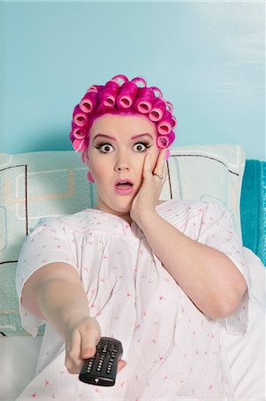 fat lady sitting - Portrait of shocked woman holding remote with hair curlers sitting on bed Stock Photo - Premium Royalty-Free, Code: 693-06120724