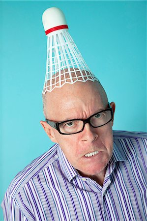Portrait of angry senior man with shuttlecock on head over colored background Stock Photo - Premium Royalty-Free, Code: 693-06120721
