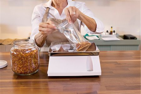 Close-up of a female employee measuring spice on weight scale in store Stock Photo - Premium Royalty-Free, Code: 693-06120776