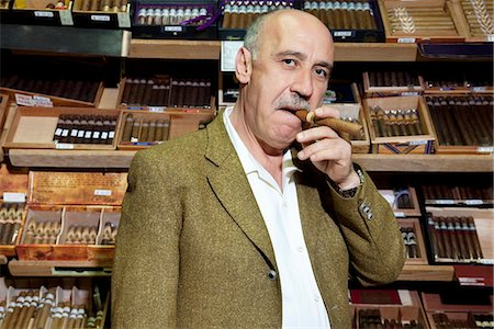 Portrait of mature tobacco shop owner smoking cigar in store Stock Photo - Premium Royalty-Free, Code: 693-06120797
