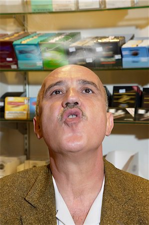 Mature man in tobacco store blowing smoke Stock Photo - Premium Royalty-Free, Code: 693-06120804