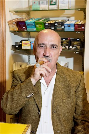 Portrait of mature tobacco store owner smoking cigar Stock Photo - Premium Royalty-Free, Code: 693-06120805