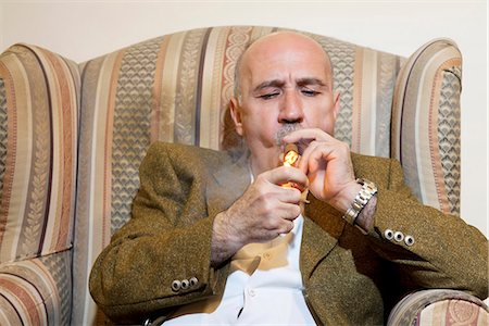 Mature man igniting cigar while sitting on armchair Stock Photo - Premium Royalty-Free, Code: 693-06120802