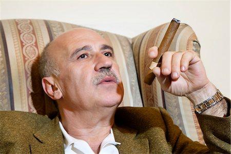 Mature man smoking cigar while relaxing on armchair Stock Photo - Premium Royalty-Free, Code: 693-06120803