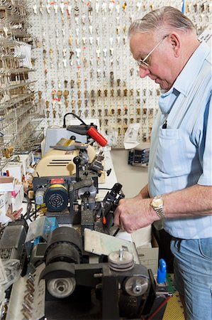 Side view of locksmith working in key store Stock Photo - Premium Royalty-Free, Code: 693-06120839
