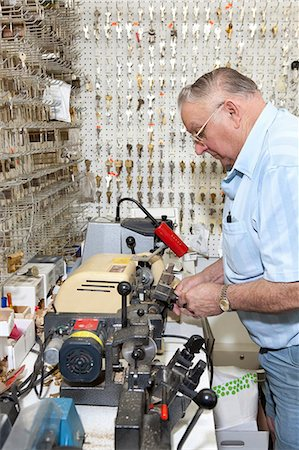 Side view of senior locksmith making key in store Stock Photo - Premium Royalty-Free, Code: 693-06120841