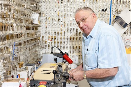 Senior locksmith looking away while making key in store Stock Photo - Premium Royalty-Free, Code: 693-06120842
