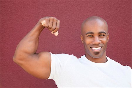 Portrait of a young African American man flexing muscles over colored background Stock Photo - Premium Royalty-Free, Code: 693-06120982