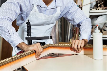 Midsection of a young craftsman working on picture frame's corner Stock Photo - Premium Royalty-Free, Code: 693-06121002