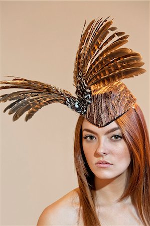 feather  close-up - Portrait of a young woman wearing feathered headdress on colored background Stock Photo - Premium Royalty-Free, Code: 693-06121188