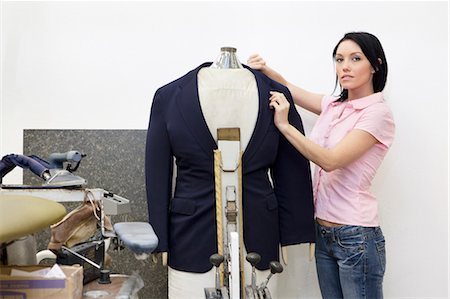 Portrait of a mid adult woman dressing mannequin Stock Photo - Premium Royalty-Free, Code: 693-06121204