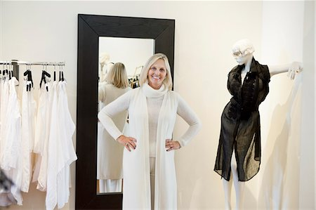 Portrait of a happy senior woman trying on clothes in fashion boutique Stock Photo - Premium Royalty-Free, Code: 693-06121214