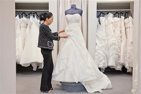Side view of a mature employee adjusting elegant wedding dress in bridal store Stock Photo - Premium Royalty-Free, Code: 693-06121245