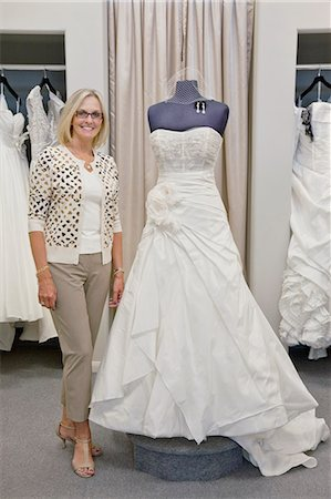 Portrait of a happy woman standing by elegant bridal dress in boutique Stock Photo - Premium Royalty-Free, Code: 693-06121240