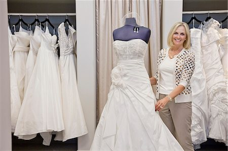 Portrait of a happy senior female adjusting wedding dress on mannequin in bridal store Stock Photo - Premium Royalty-Free, Code: 693-06121242