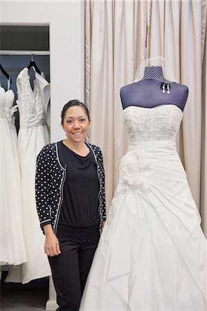 Portrait of a mature employee standing by elegant wedding dress in bridal store Stock Photo - Premium Royalty-Free, Code: 693-06121243