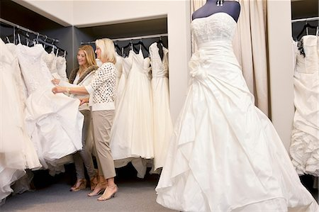 Happy mother and daughter shopping together for wedding gown in boutique Stock Photo - Premium Royalty-Free, Code: 693-06121252
