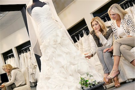 Mother and daughter sitting on sofa while looking at elegant wedding dress in bridal store Stock Photo - Premium Royalty-Free, Code: 693-06121272