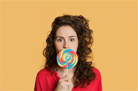 Portrait of a young woman holding lollipop in front of face over colored background Stock Photo - Premium Royalty-Free, Code: 693-06121347