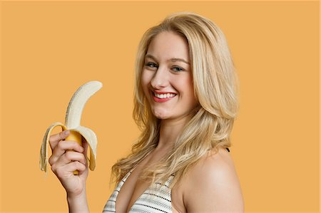 Portrait of a young woman eating banana over colored background Stock Photo - Premium Royalty-Free, Code: 693-06121373