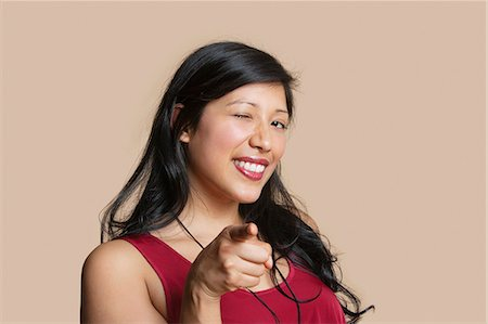 expressive - Portrait of a young woman pointing while winking over colored background Stock Photo - Premium Royalty-Free, Code: 693-06121386
