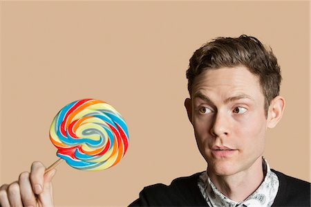 Mid adult man looking at lollipop over colored background Stock Photo - Premium Royalty-Free, Code: 693-06121398