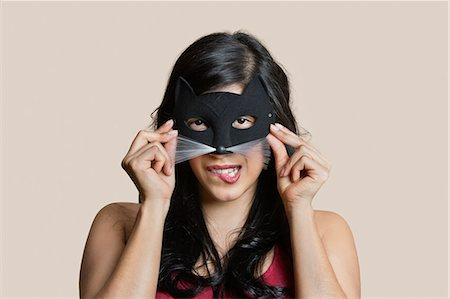 Portrait of a young woman wearing eye mask while biting lip over colored background Stock Photo - Premium Royalty-Free, Code: 693-06121404