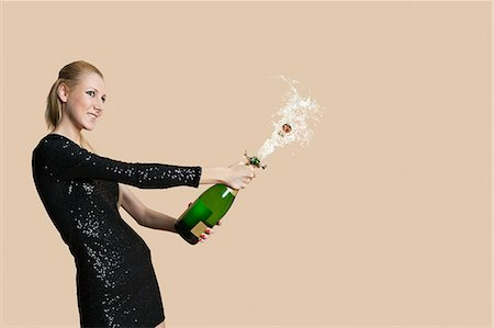 Beautiful young woman uncorking champagne bottle over colored background Stock Photo - Premium Royalty-Free, Code: 693-06121417