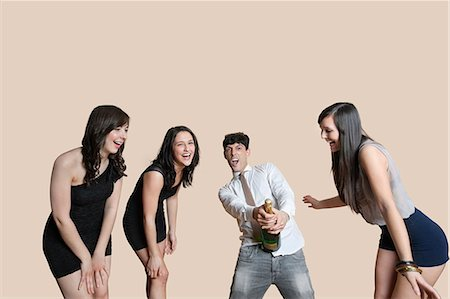 Young friends opening champagne bottle over colored background Stock Photo - Premium Royalty-Free, Code: 693-06121428