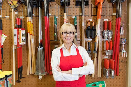 Portrait of a happy senior woman with arms crossed in front of gardening tool Stock Photo - Premium Royalty-Free, Code: 693-06324027