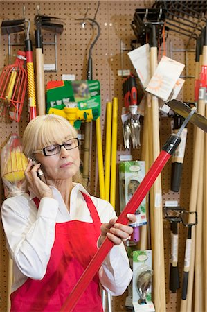 Senior female employee holding gardening tool while using mobile phone Stock Photo - Premium Royalty-Free, Code: 693-06324029