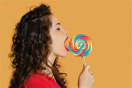 Side view of a young woman licking lollipop over colored background Stock Photo - Premium Royalty-Free, Code: 693-06324106