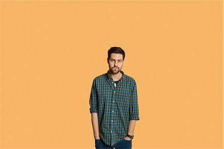 Portrait of a young man standing with hands in pockets over colored background Stock Photo - Premium Royalty-Free, Code: 693-06324109