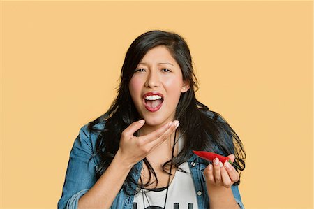 spicy - Portrait of a young woman eating red hot chili pepper over colored background Stock Photo - Premium Royalty-Free, Code: 693-06324124