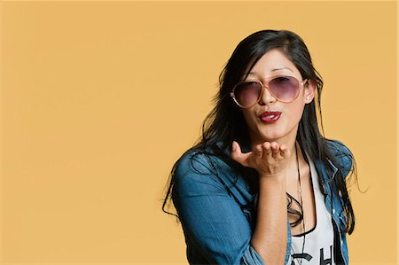 Young woman blowing kisses over colored background Stock Photo - Premium Royalty-Free, Code: 693-06324120