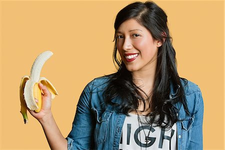 Portrait of a young woman with banana over colored background Stock Photo - Premium Royalty-Free, Code: 693-06324121