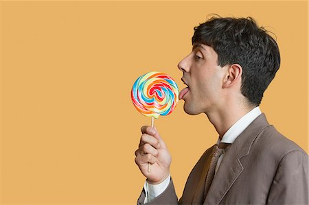 Side view of young businessman licking lollipop over colored background Stock Photo - Premium Royalty-Free, Code: 693-06324141