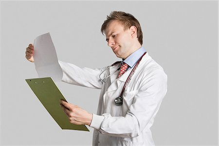 report - Male doctor in a lab coat reading medical records over gray background Stock Photo - Premium Royalty-Free, Code: 693-06324212