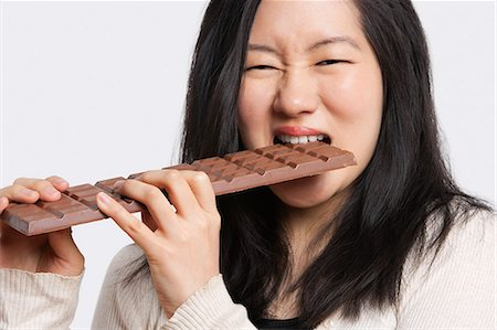 desire - Portrait of a young woman eating a large chocolate bar over light gray background Stock Photo - Premium Royalty-Free, Code: 693-06324271