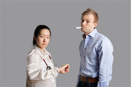 Portrait of a patient with thermometer in mouth standing with doctor Stock Photo - Premium Royalty-Free, Code: 693-06324287