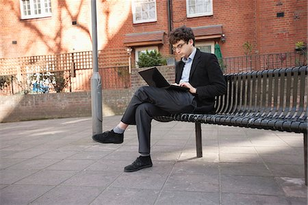 people sitting on bench - Young businessman using laptop while sitting on bench Stock Photo - Premium Royalty-Free, Code: 693-06324321